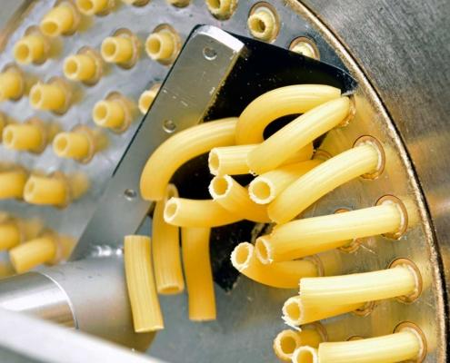 Die Nudeln werden in Form gepresst und sofort auf die richtige Länge geschnitten